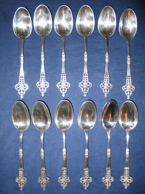 "Spoons in a Renaissance style richly decorated with pierced clover and a central head on the handle and a ""queue de rat"" relief pattern on the back."