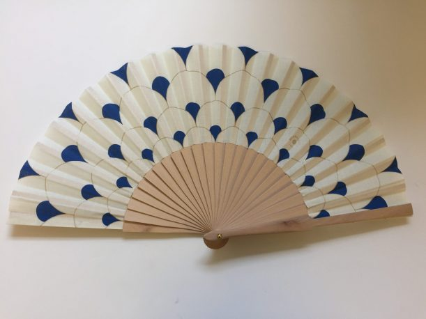 Fan with cream blue and gold tiles design and wooden sticks. Undated.