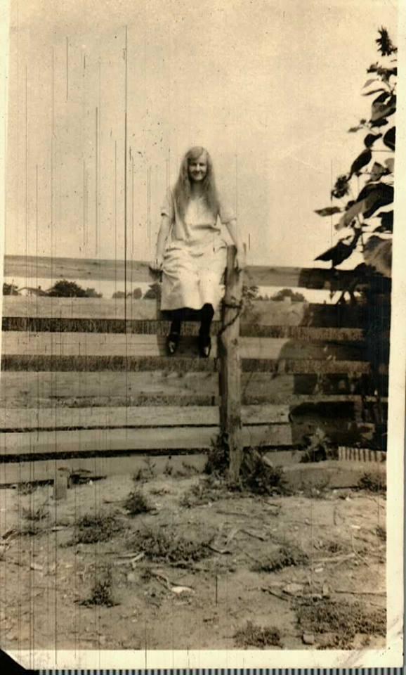 Girl sitting on a fence, Wentzville, Missouri. Undated.
