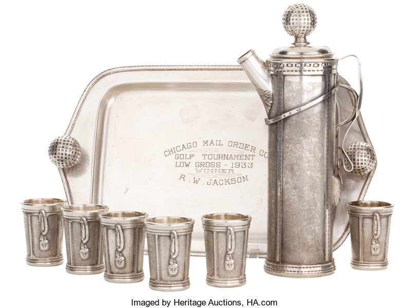 Martini pitcher in a golf bag design and golf ball cap. Six cups and tray included. ca. 1926.
