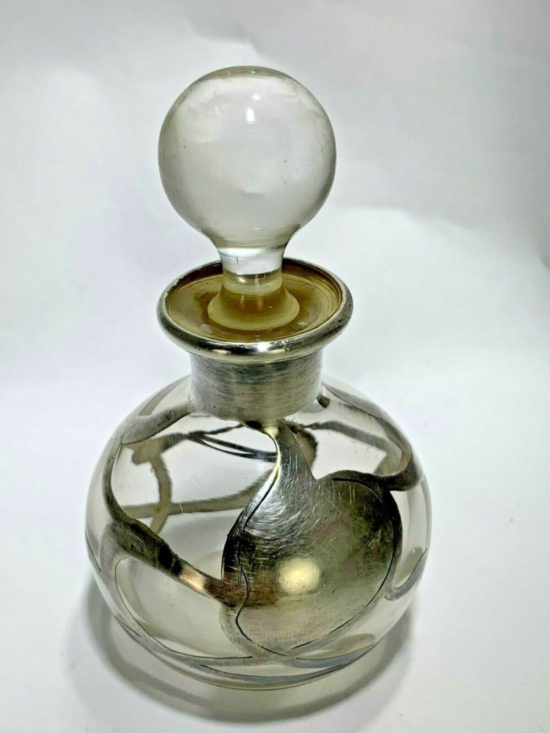 Clear glass perfume bottle with sterling silver overlay in a foliage design. Art Deco. Glass and sterling silver. Maker not known.