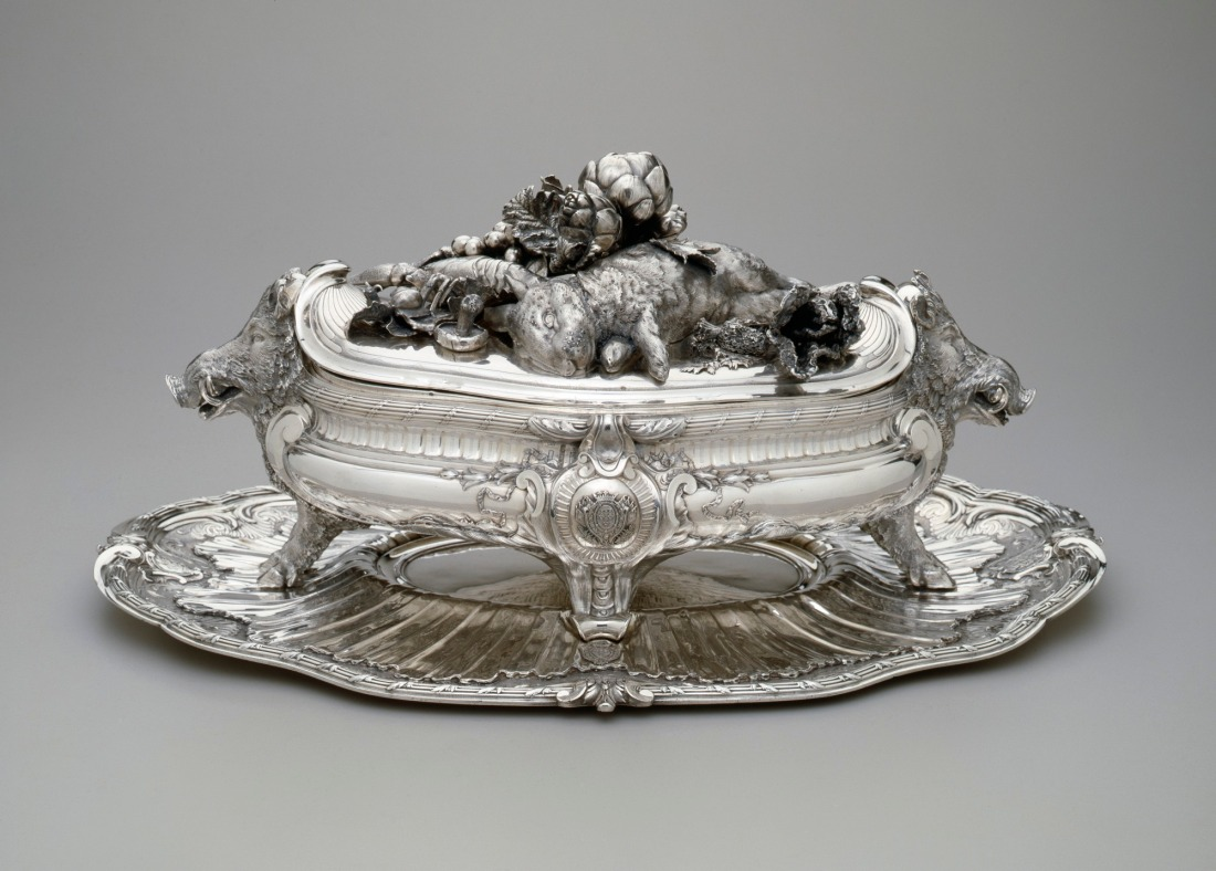 Tureen with lid with boar's heads and forelegs ornamenting either end with vegetables, crustaceans, and other game on the lid.