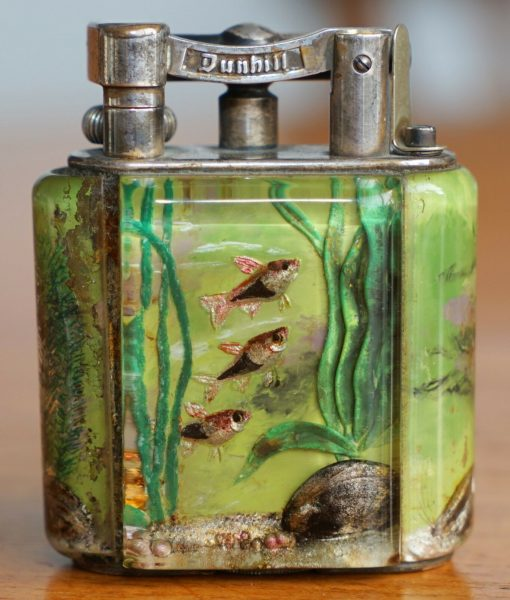 Aquarium table lighter with green water and silver colored fish. 1950's.