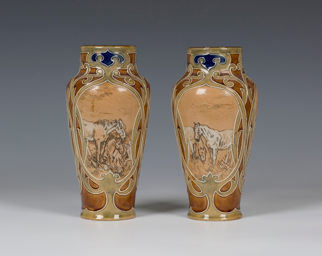 Stoneware vases with high shouldered bodies, monogrammed with three panels of horses within green stylized foliate framing against a light brown ground. Early 20th c.