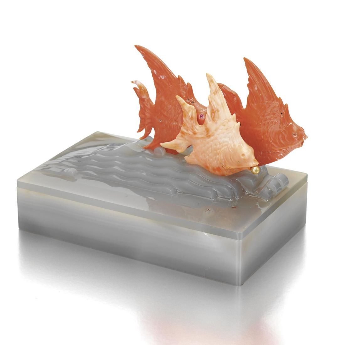 Carved agate rectangular cigarette box surmounted by three carved coral tropical fish.