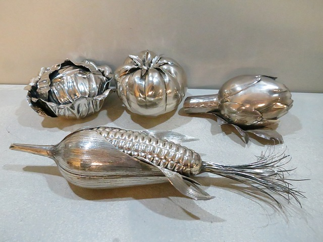 Four table lighters in the form of an artichoke, cauliflower, corn on the cob and a tomato. Three are signed. Mid 20th c.