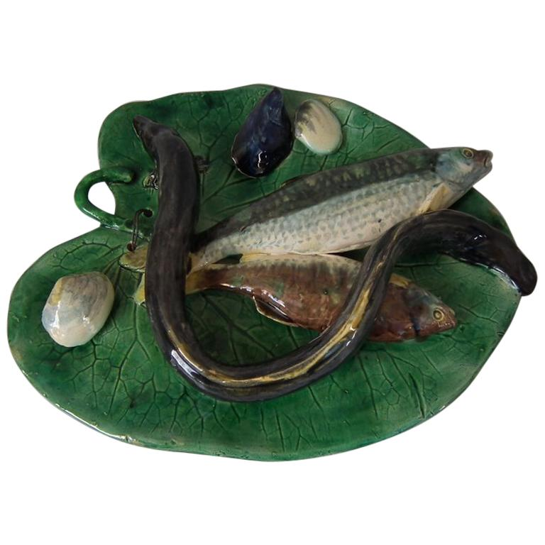 Wall plaque or plate featuring an eel, fish and shellfish sitting on a leaf.