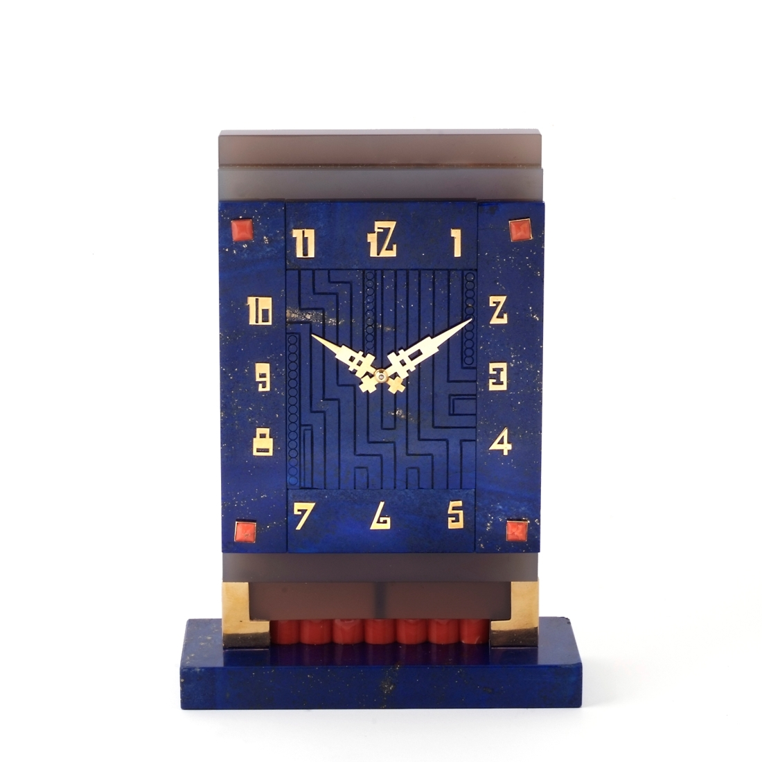 Desk clock. Carved lapis lazuli clock face with applied yellow gold Arabic numerals and openwork hands. Stepped agate surround with a lapis lazuli and gold base with coral.  ca. 1929.