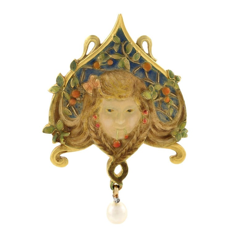 Brooch. Motif of a stylized shield with a maiden's face with flowing blonde hair. Decorations of cherries and vines. ca. 1900.