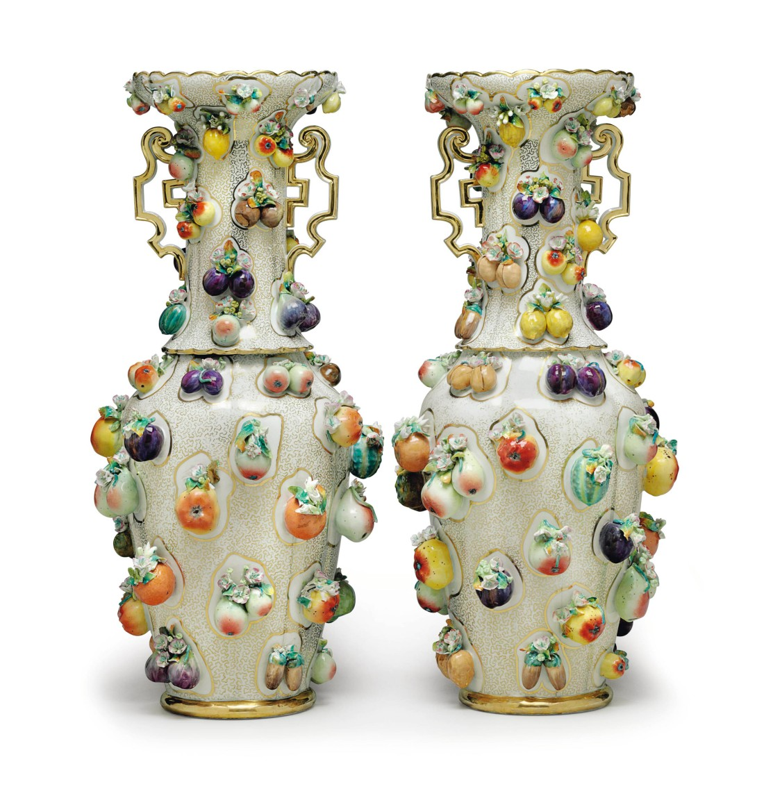 Pair of baluster form vases with scalloped gilt rims and scrolled handles. Fruit applied all over on a a gilt vermiculé ground.