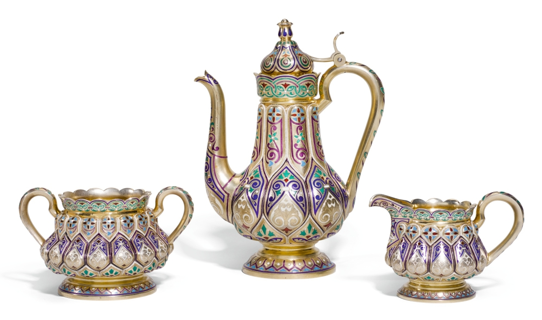 Three piece silver-gilt and champlevé enamel coffee set with coffee pot, sugar bowl and creamer decorated in an Oriental pattern with traditional scrolling ornaments in shades of white, blue and green. 1898-1908.