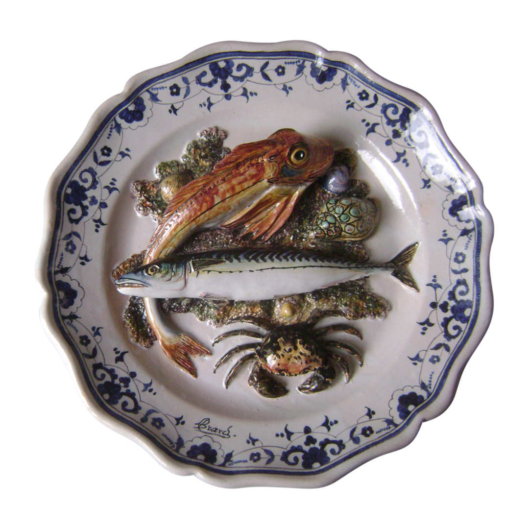 Round dish with polychrome decoration of a crab and two fish in relief in the center.